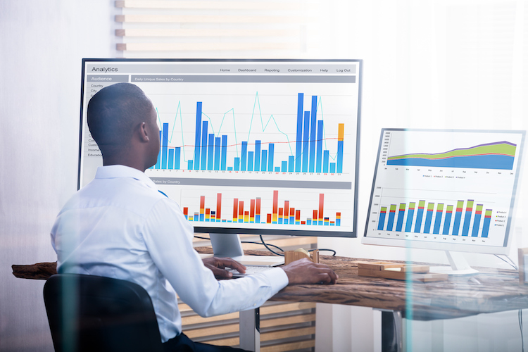 A data analyst sits at his desk working with graphs and other data analytics tools on multiple computer monitors.