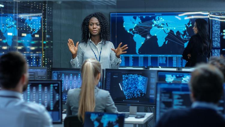 A woman standing in front of a group of people using computers