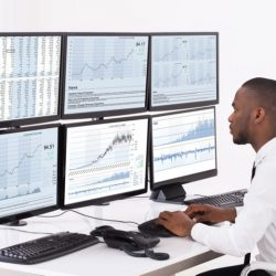 A research analyst monitors data on several screens.
