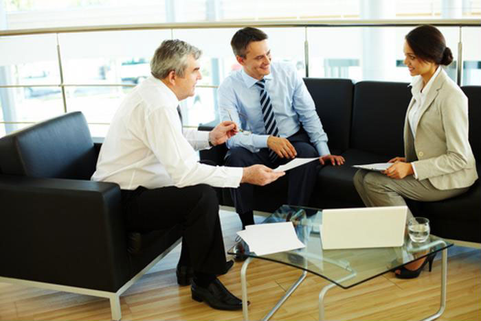 Executives in professional dress sitting together, having a discussion.