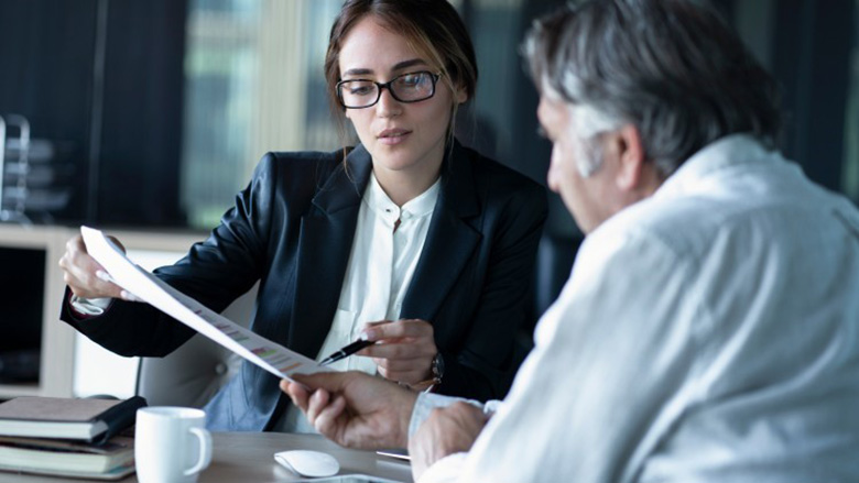 A business intelligence consultant reviews a report with a client.