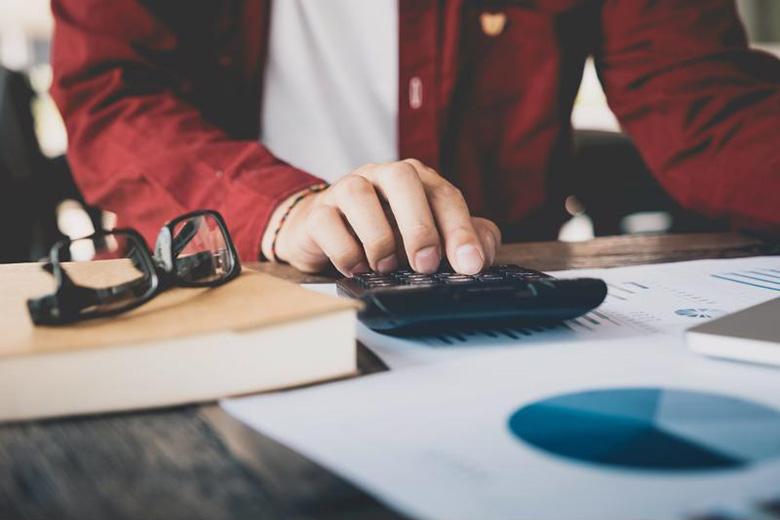 A man uses a calculator at a desk.