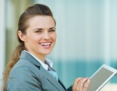 woman on tablet smiling at camera