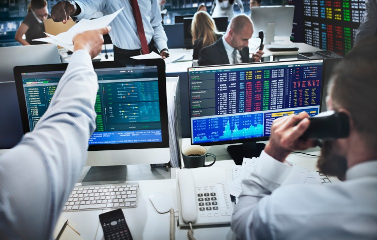 A team of brokers trading on the stock market via desktop computers.