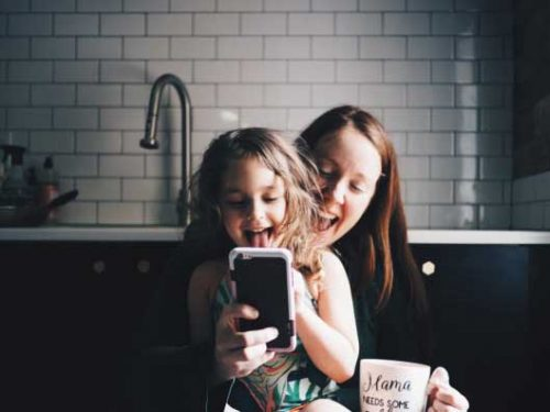 Mother and daughter use smartphone in kitchen