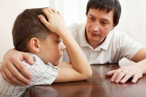 Father comforts sad son