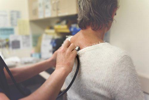 A nurse listens to a patient's heart beat.
