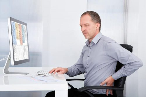 Man sitting in desk chair clutching his lower back in front of a computer, his work being interrupted by apparent back pain
