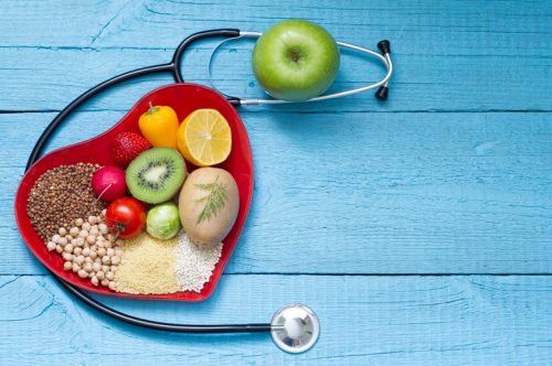 Healthy foods sit on a table with a stethoscope