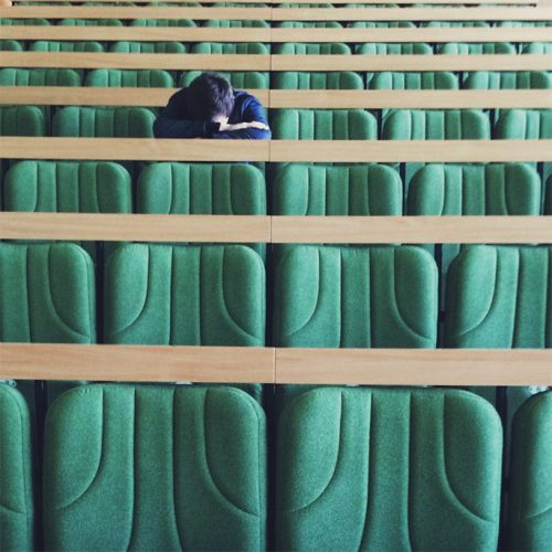 Student with head down in an empty classroom