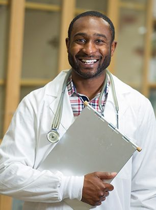 Male doctor smiling and holding clipboard