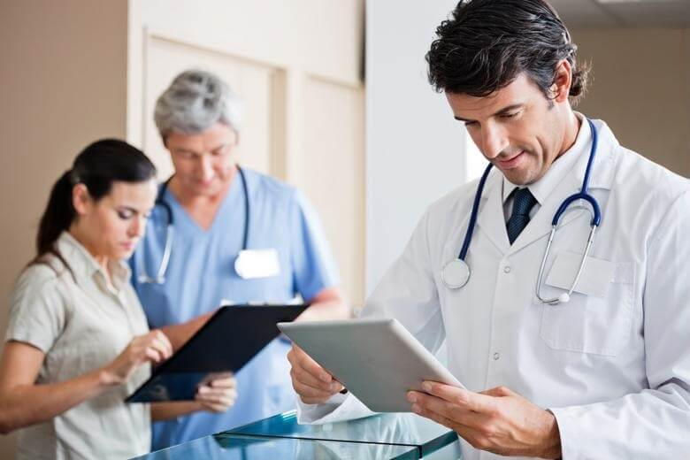 Three medical professionals using tablets
