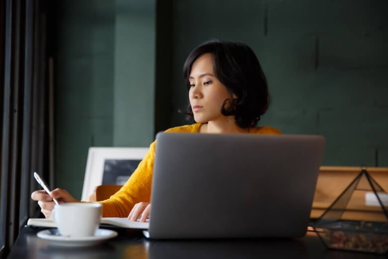 Woman using computer and taking notes