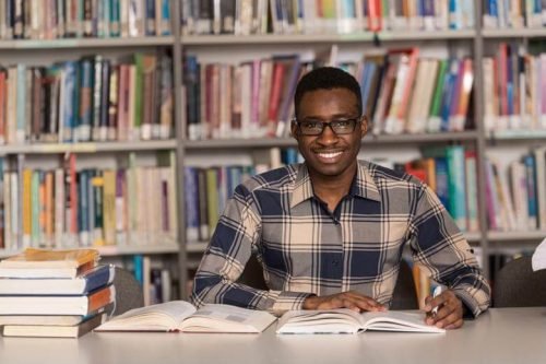 An online MSN-FNP student studies in his local library.