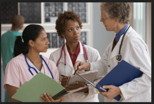 Three health care professionals discuss a patient.