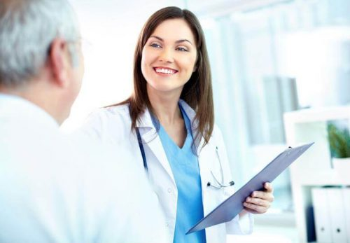 DNP nurse smiling with clipboard in hand.