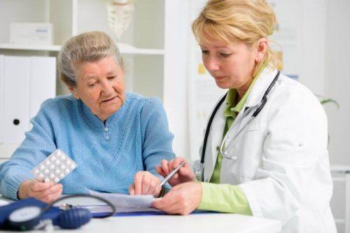 Nurse practitioner talking to elderly patient