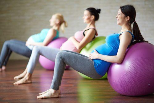 Pregnant women with exercise balls enjoy a prenatal care class.