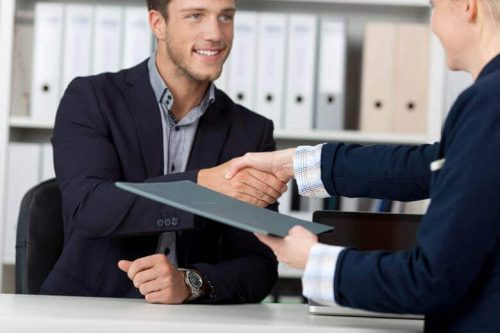 A job candidate shakes hands with a university hiring manager