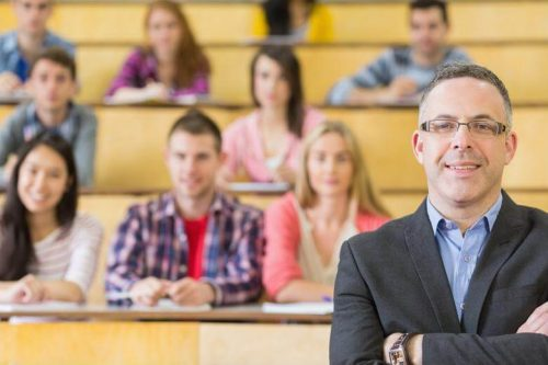A dean stands in front of students in a lecture hall.
