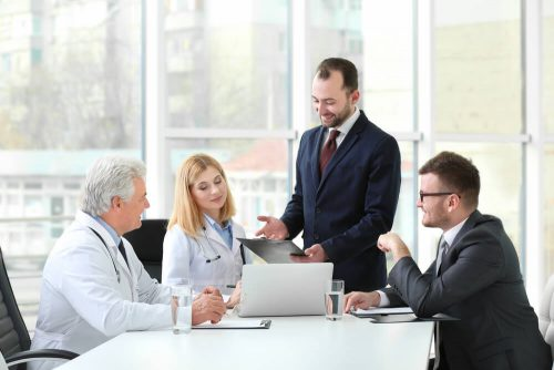 Health care executives talk during a meeting.