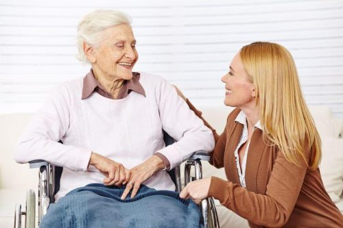 A nursing home administrator visits with a resident.