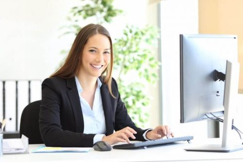 A higher education administrator types on her computer