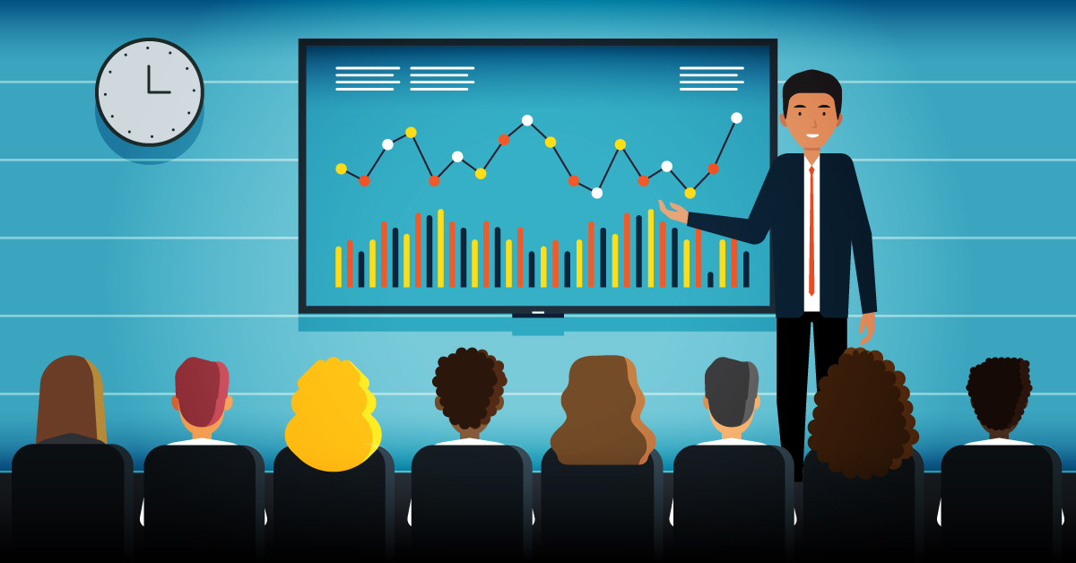 : A corporate trainer stands in front of a large visual as a group of employees sits in the audience.