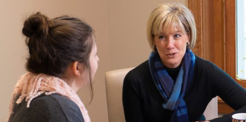 Female faculty member talks with student