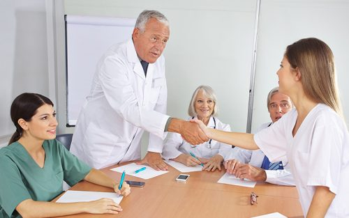 Older male doctor shakes hands with colleague