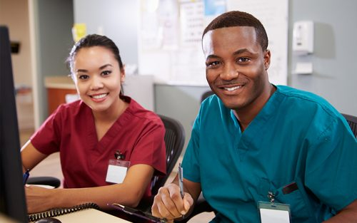 Two nurses smiling at viewer