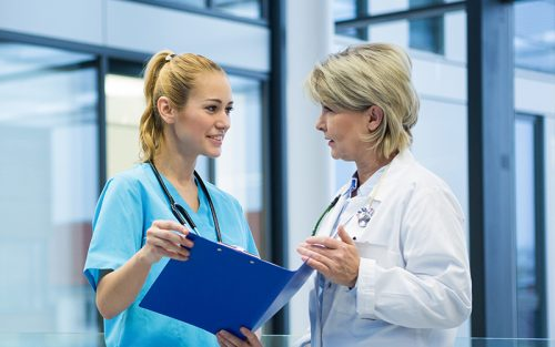 Doctor and nurse talking in hospital hallway