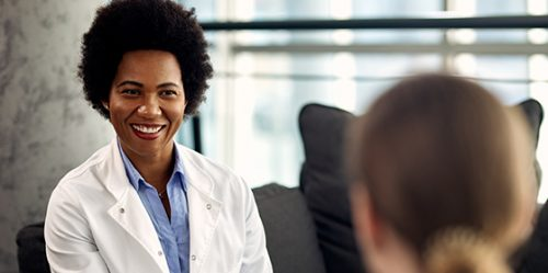 Happy black female counselor communicating with patient