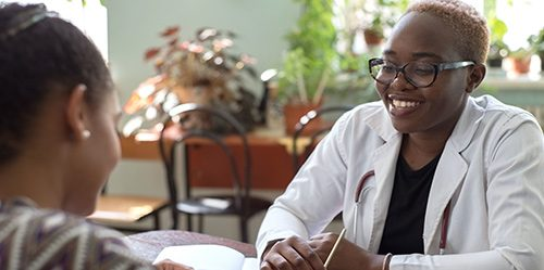 Young Black female doctor sits at a desk with a patient and fills out a form