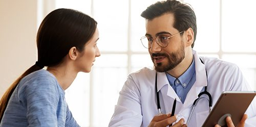 Younger male doctor consults with female patient