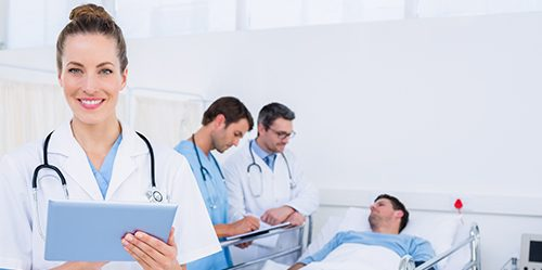 Female NP holding clipboard while patient is in bed in the background