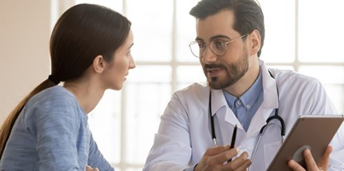 Male doctor with glasses speaks to female patient at a desk