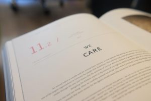 """Photograph of a textbook with a page that says """"We care"""""""