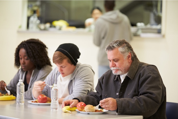 Group of people eating a meal in a cafeteria