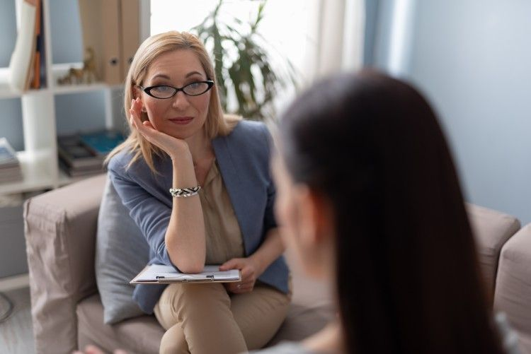A crisis counselor helps a client while sitting on a couch.