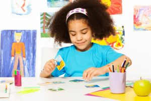 A child sits at a table with artwork on the wall behind her playing a matching card game.