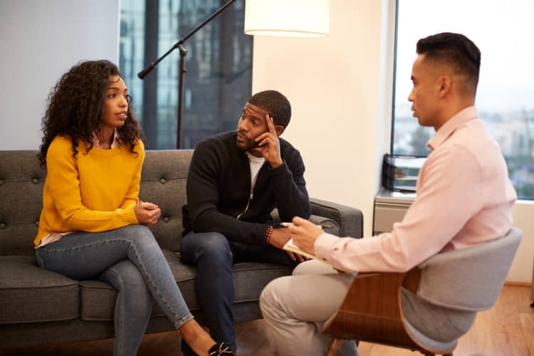 A marriage and family therapist counsels a couple.