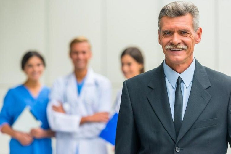a male in a suit standing in front of some healthcare professionals wearing scrubs