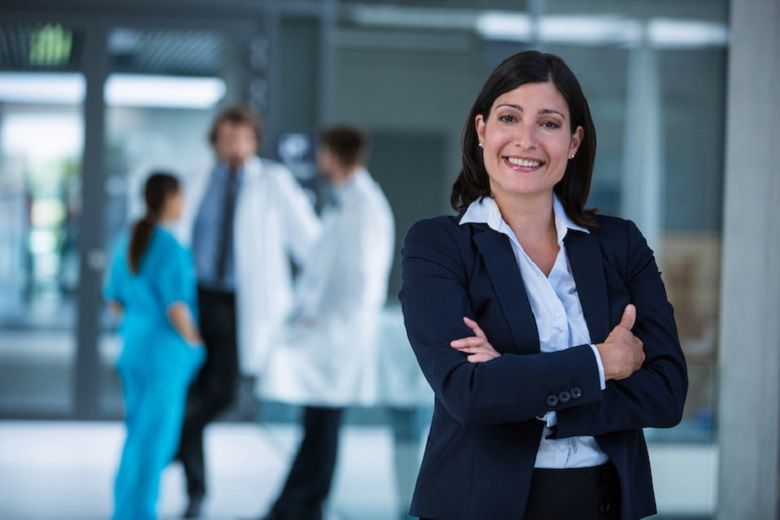 healthcare professional poses in front of a hospital