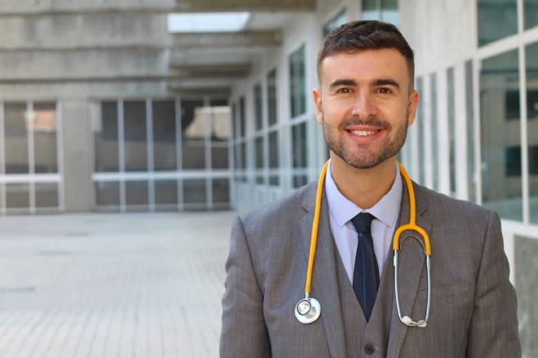 Hospital CEO poses in front of a hospital in business attire with a stethoscope