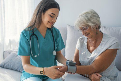 A nurse checks the pulse of an elderly woman patient.