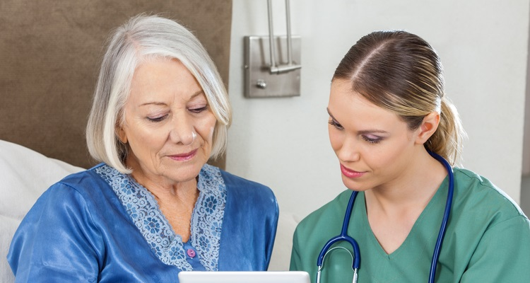 Female nurse talks with female patient in hospital room.