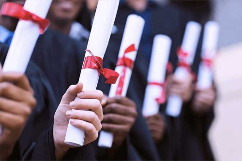 Up close image of a graduates holding diplomas