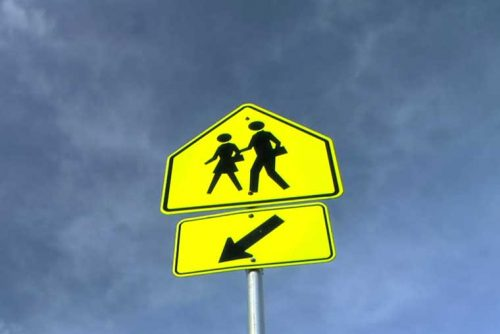 Up close image of a school crossing sign