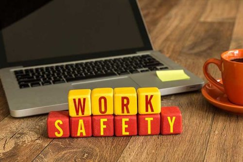 Block letters spelling Work Safety in front of a laptop
